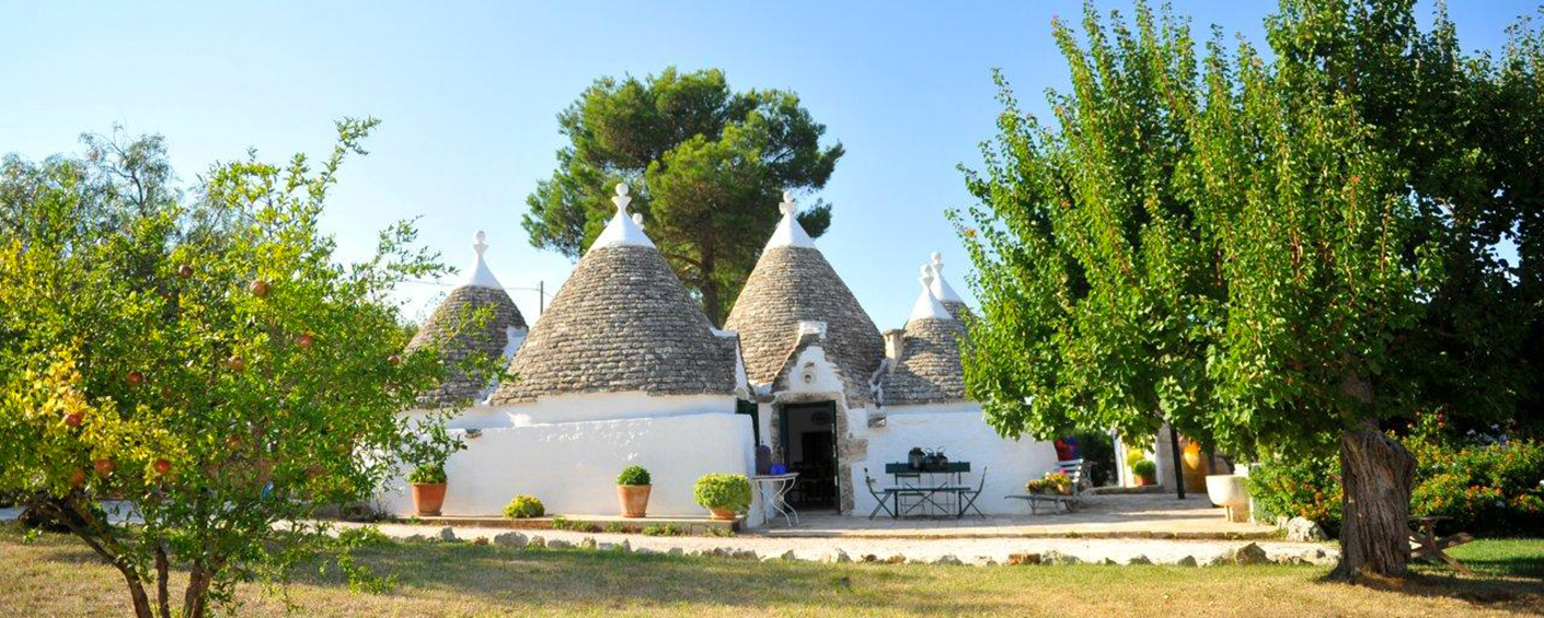 The solitary Apulian trullo with its high cone-shaped roof set in a lush garden with pool